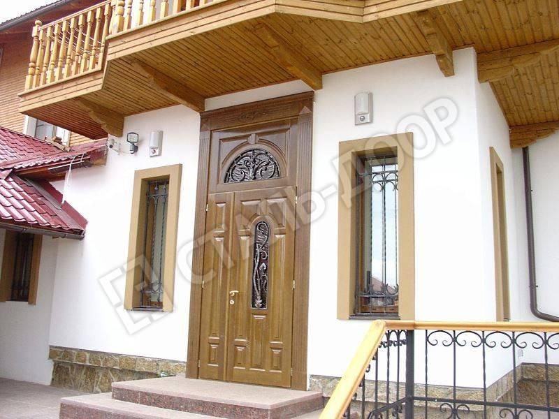 Входная дверь для загородного дома с отделкой массивом ценных пород дерева, стеклом и ковкой