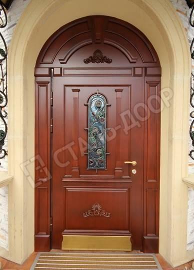 Массивная арочная дверь в частный дом со стеклом и ковкой